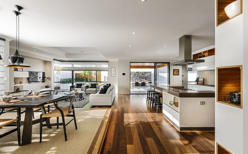 Central open space includes modern gourmet kitchen, full living room, dining space defined by beige area rug, and large swath of full height glass for natural lighting and expansive views.