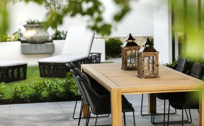 Patio features natural wood table with black wicker chairs, plus matching black wicker lounge chairs with white cushions on lawn.