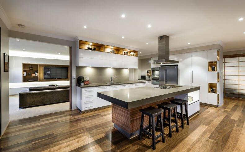 Kitchen features large, complex island including natural wood tone base, white cabinetry, large marble slab countertop with built-in range, and bar style seating space. Glossy white cabinetry surrounds, with dark marble backsplash and under-cupboard lighting.