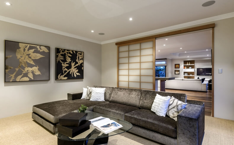 Cozy family room sits on other side of traditional shoji screens from central living space, with grey chaise lounge sectional wrapped around oblong glass topped coffee table.