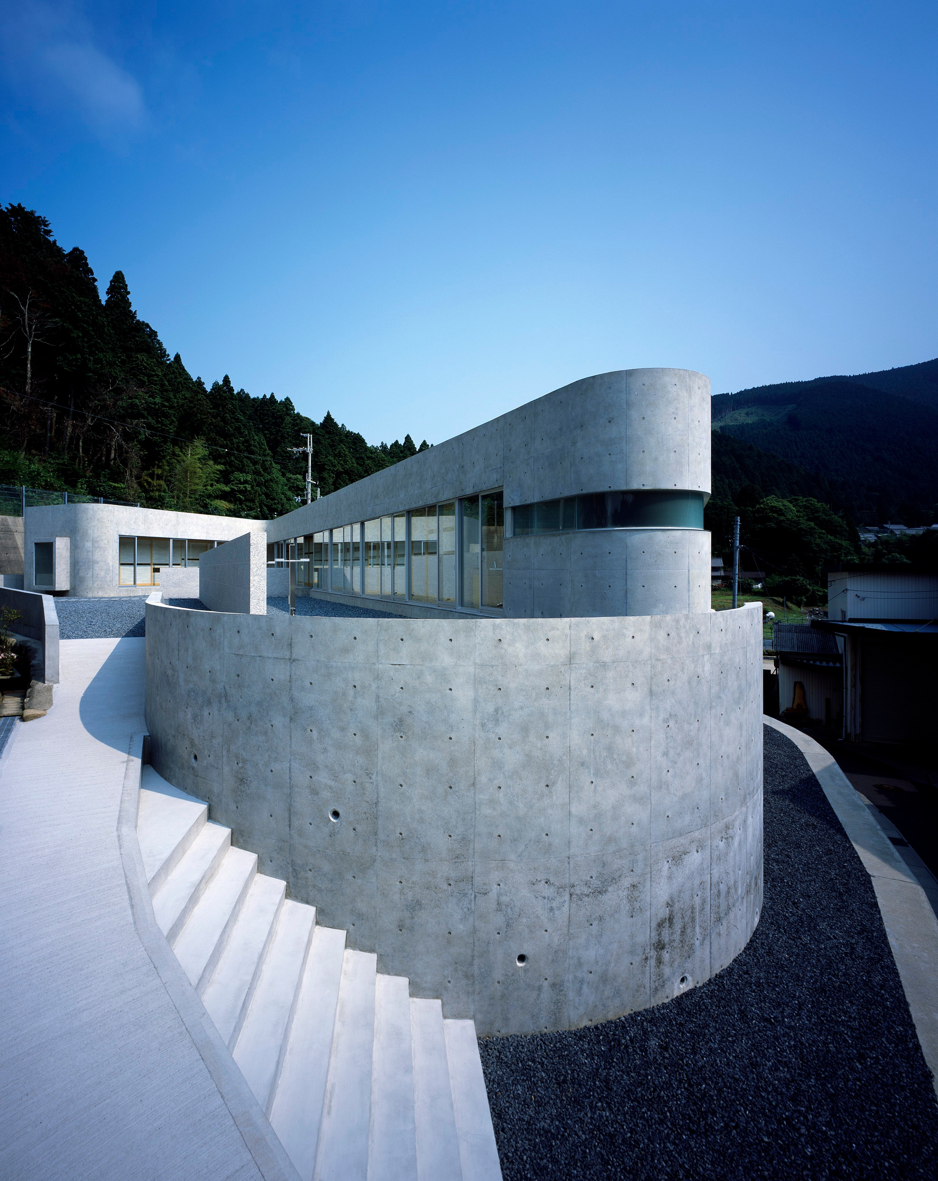 Exterior view of concrete home and exterior staircase from upper deck to lower veranda.
