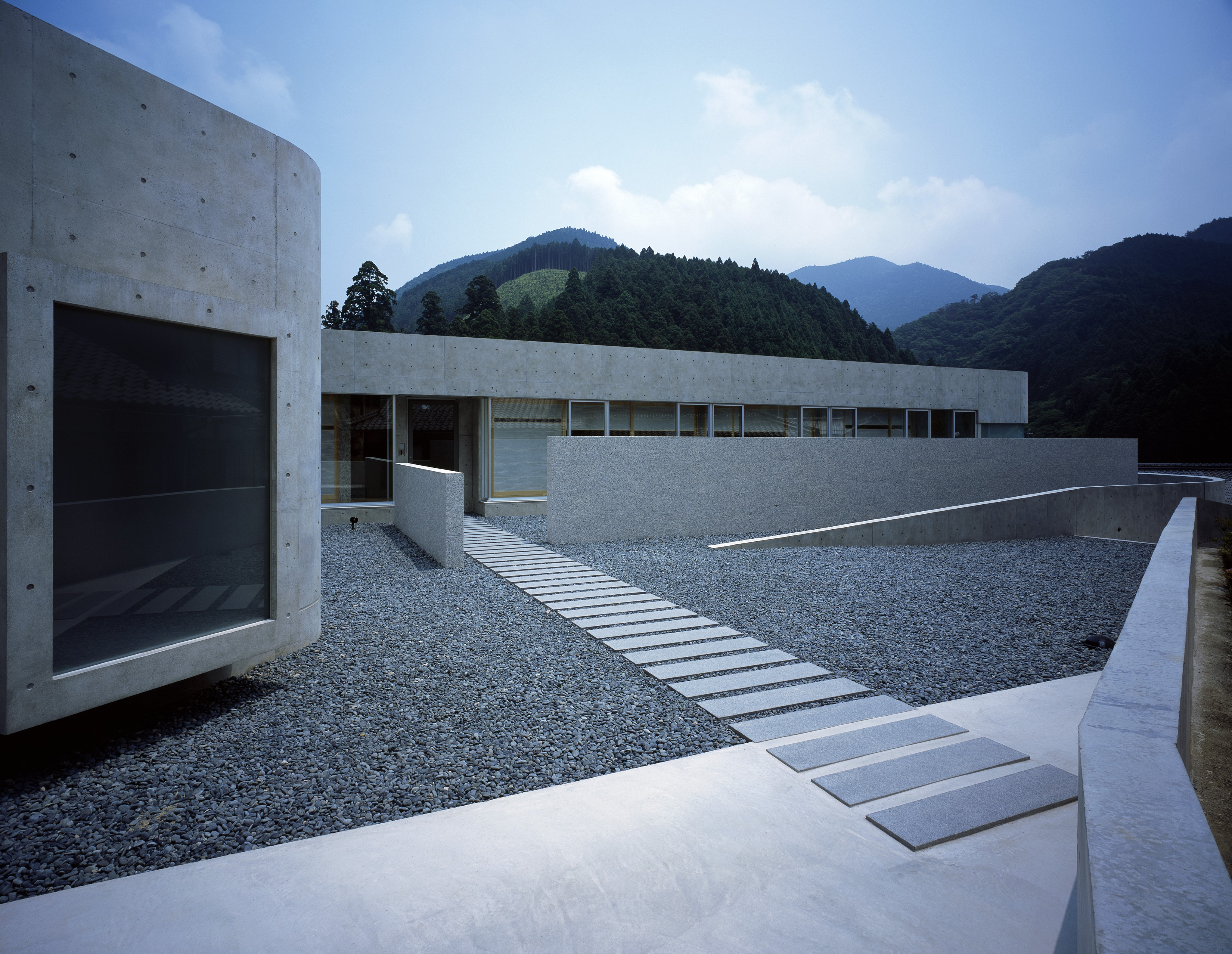 The main entrance is approached via this rectangular path over a rock garden. Windows on this side of the home are full sized.
