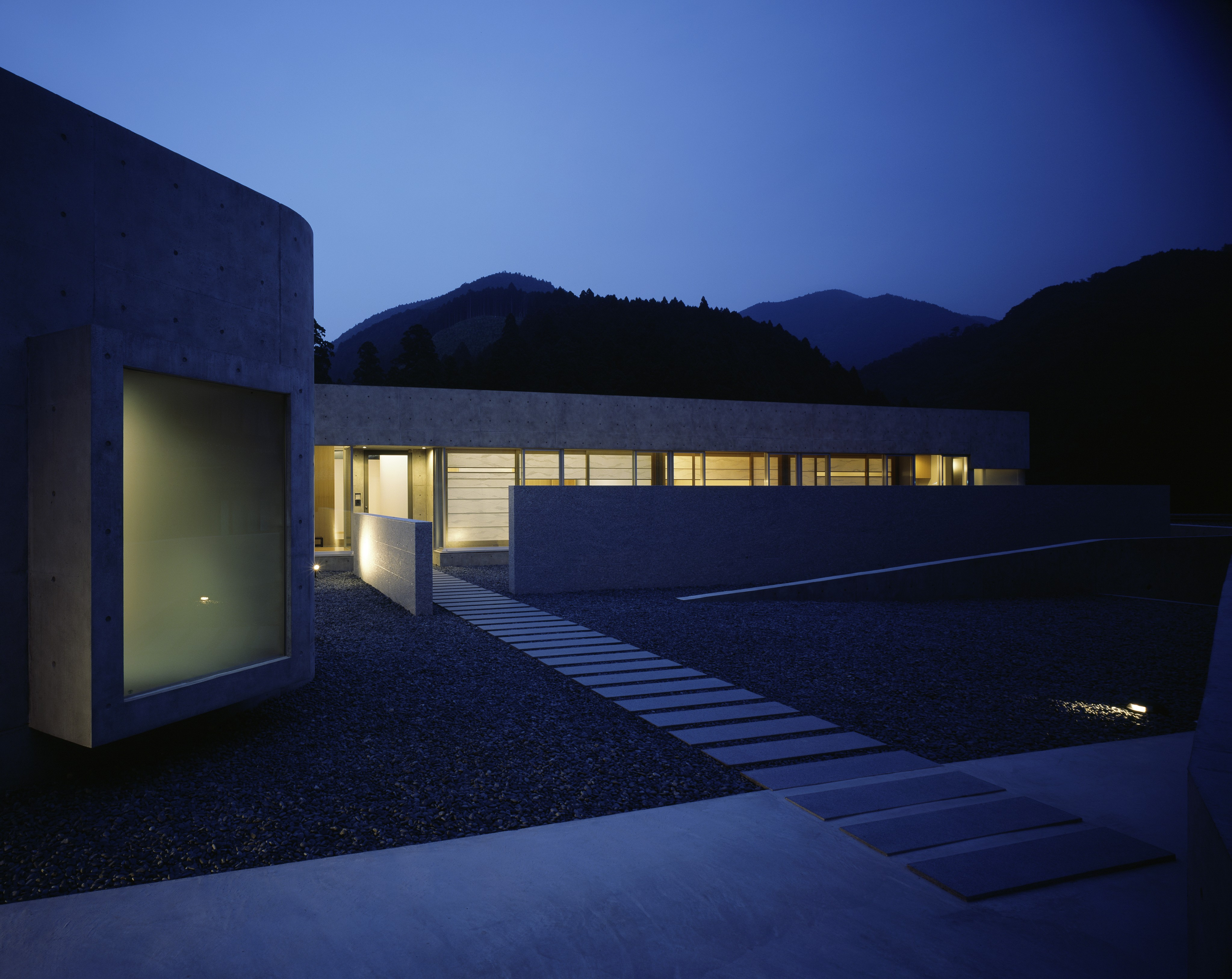 Seen at night, the interior glows brightly across the secluded patio space.