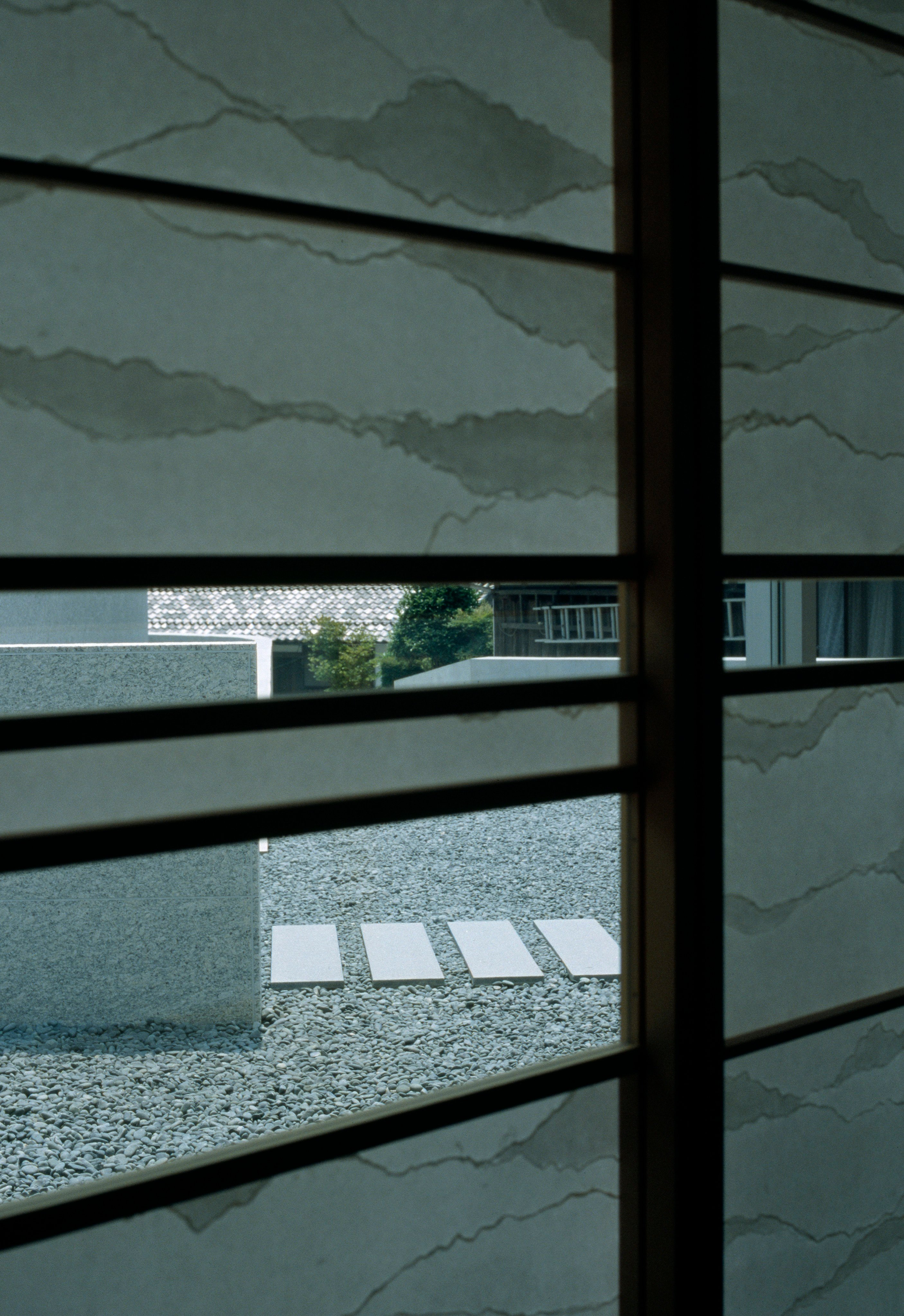 Interior view through partially obscured wood window frames toward the private patio space. Rock garden and main pathway are seen.