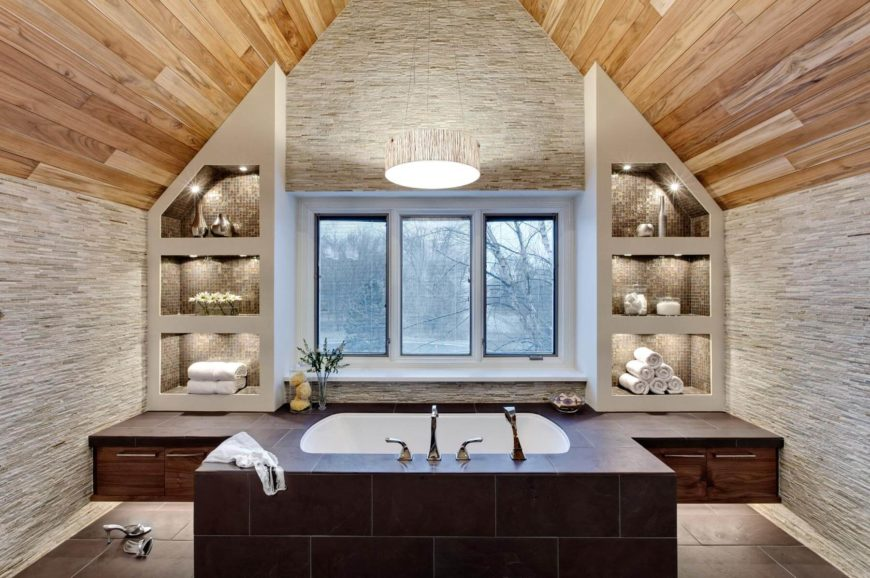 Striking, natural wood arched ceiling hangs over this both bathroom, featuring sunken tub in a tile enclosure with built-in walnut cabinetry, flanked by tile filled open shelving with built-in lighting.