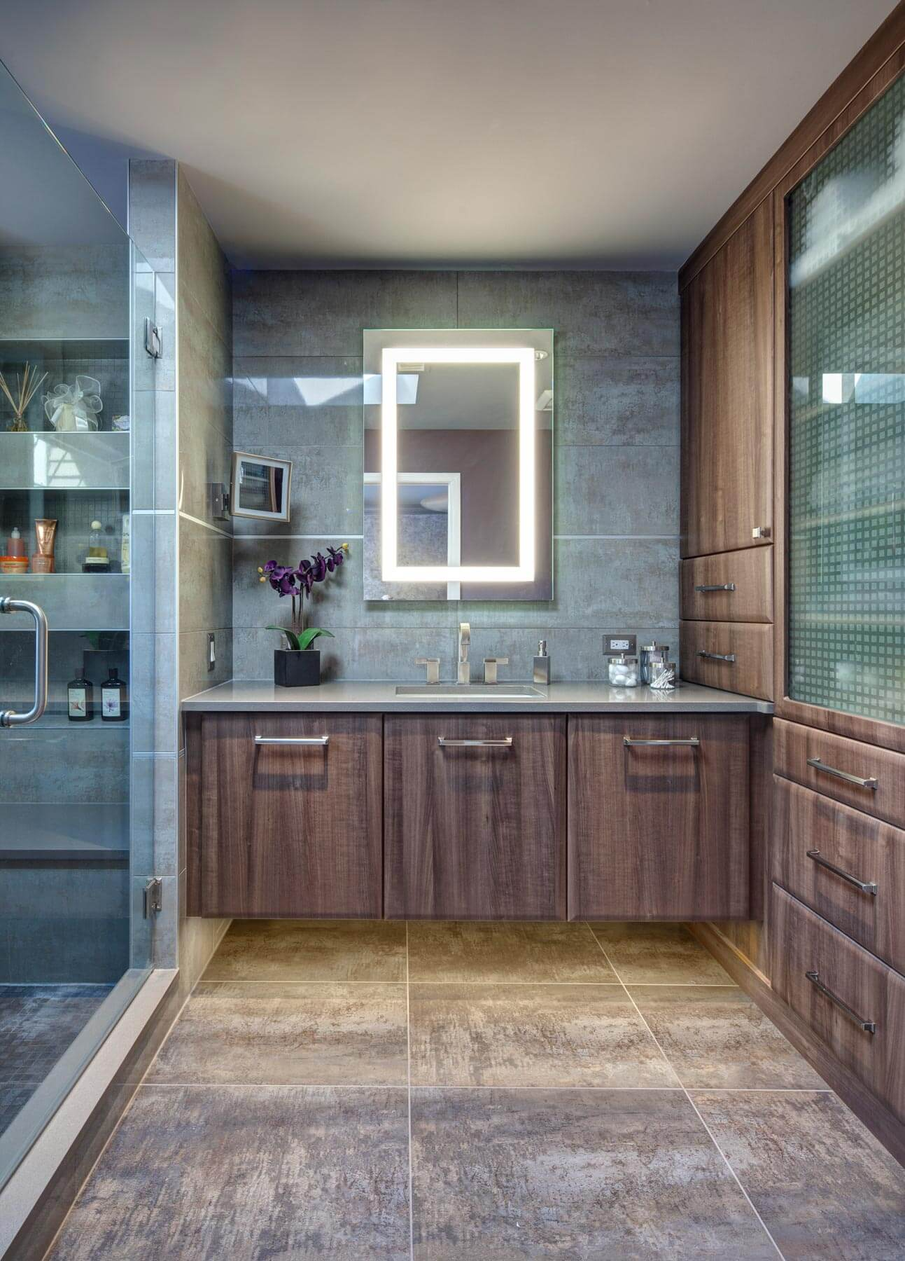 Bathroom features large format natural colored materials and a vanity mirror with internal lighting. A palate of soothing brown and blues were utilized throughout this newly remodeled primary bath, while functionality was added via an array of shower shelving and cabinetry.