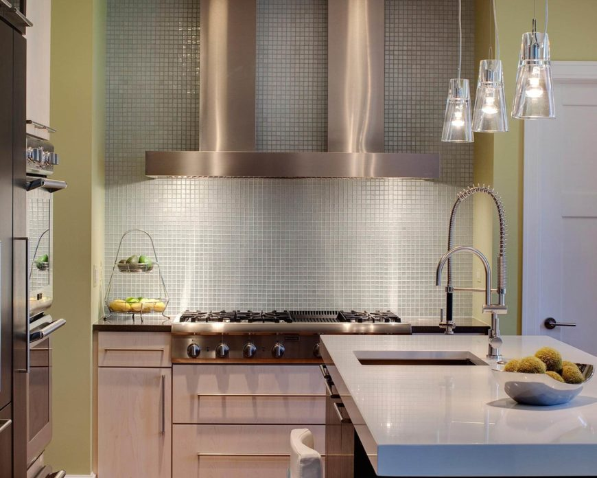 The mosaic backsplash can be seen above the range here, beneath a modern steel dual hood vent. Thick slab countertop on the island adds literal and figurative weight to the kitchen center.