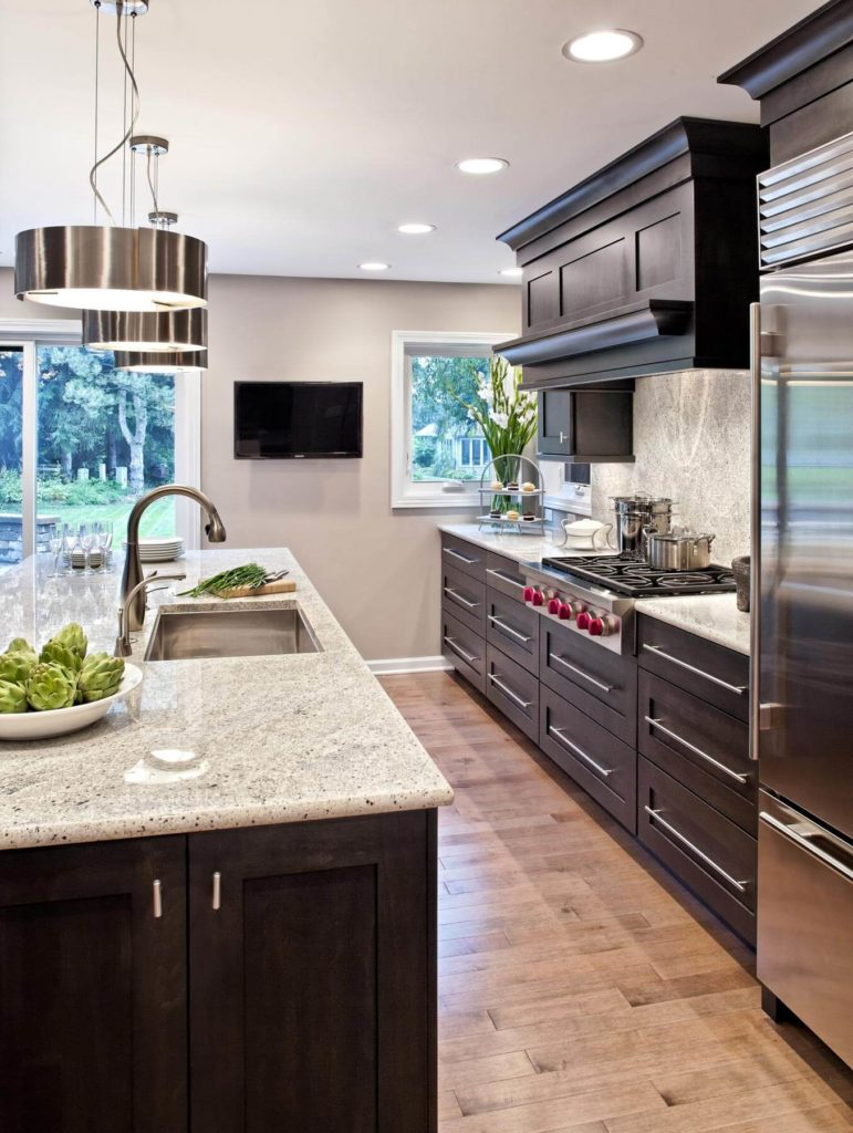 The dark wood cabinetry is balanced by a lighter toned natural hardwood floor. Minimalist steel hardware on the drawers compliments the stainless steel appliances throughout.