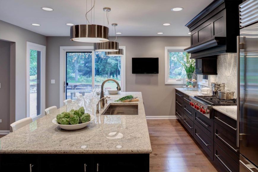 The entire space is well lit via a series of recessed ceiling lights and a trio of stainless steal cylinder chandeliers. Large windows and sliding glass door access to patio provide natural light as well.