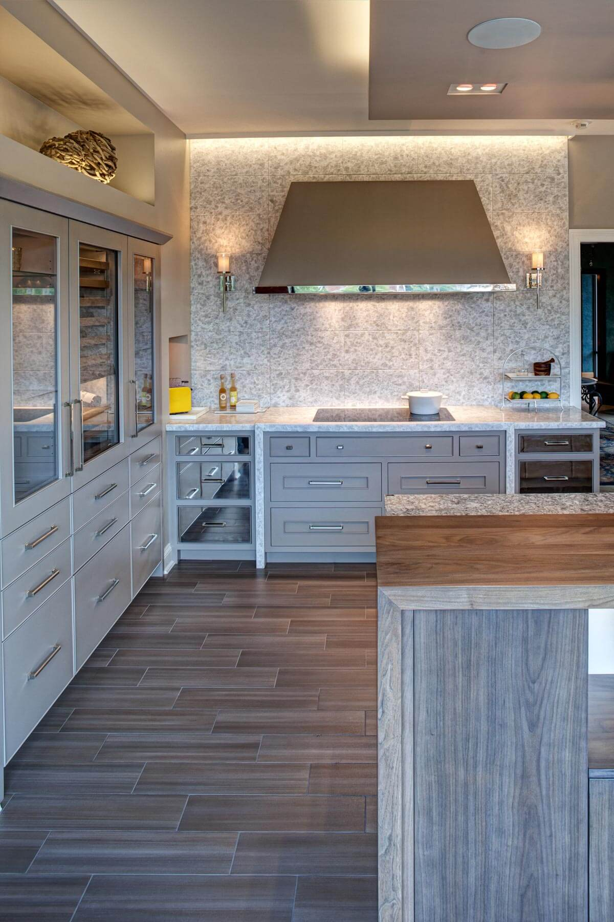 Looking over the island edge, we see the smoke colored porcelain floor tiles laid in a staggered pattern for depth, with the polished nickel drawer fronts flanking the cooking space.
