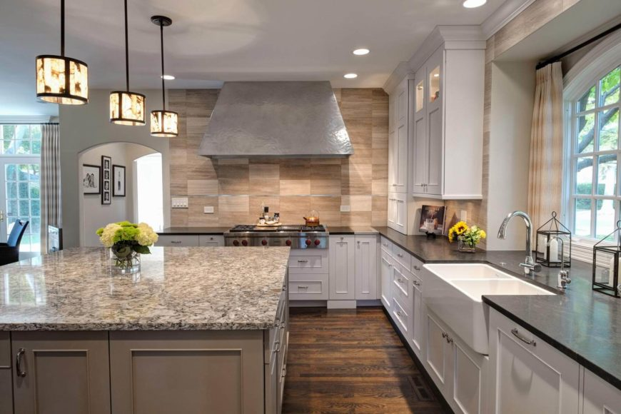 The neutral stone backsplash surrounding the zinc hood stands out in the room. Details like the extra-size white basin sink and pewter countertop insert add interesting detail and function.