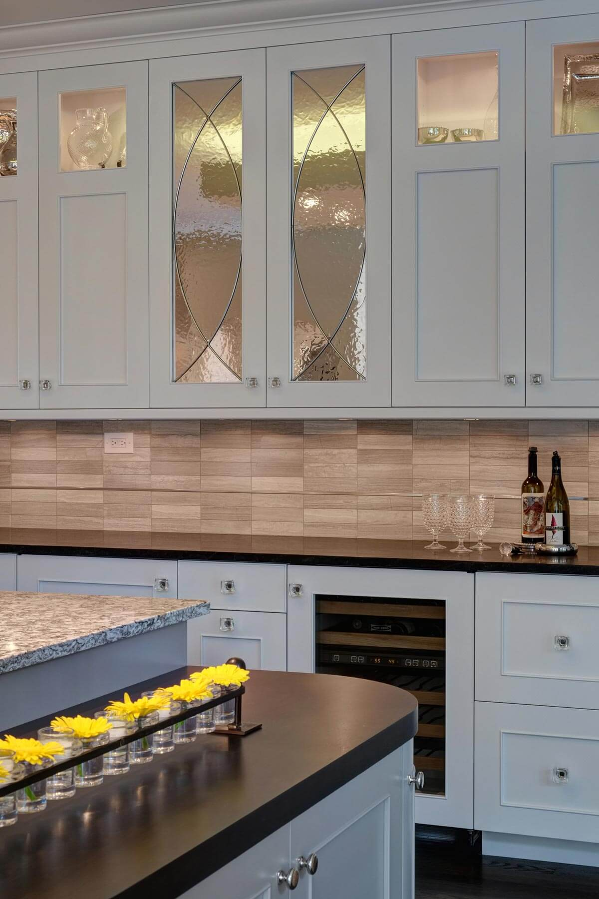 """Lower tier on the """"homework"""" island features matching black granite countertop and rounded edges. Above the countertops we see the stone backsplash with single strip detail."""