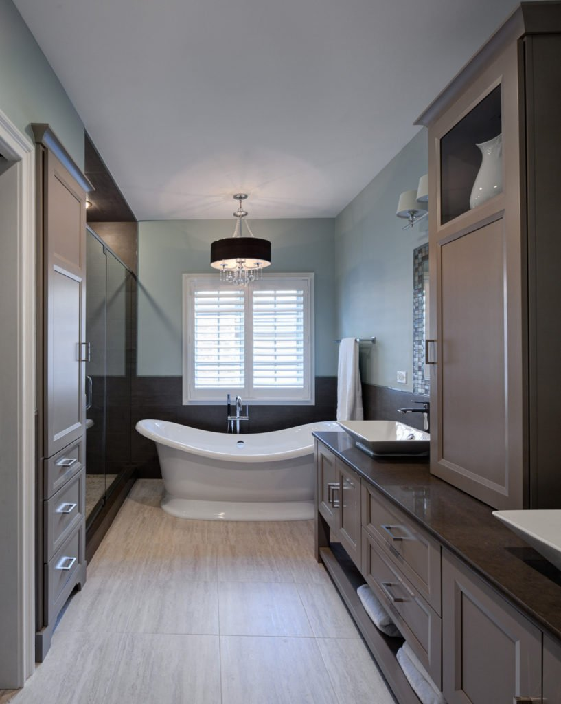 Lengthy narrow bathroom is packed with taupe painted cabinetry and stone floor tiles, with mosaic tiles wrapping vanity mirrors at right, hanging over white angular vessel sinks. Hidden shelving sits below drawers, while brilliant curved white pedestal tub commands attention at center.
