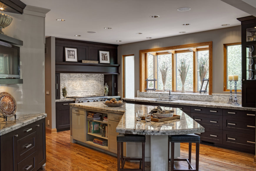 L-shaped island with marble top, matching the countertops and backsplash throughout the kitchen, stands with ample cabinetry, shelving, and dining space.