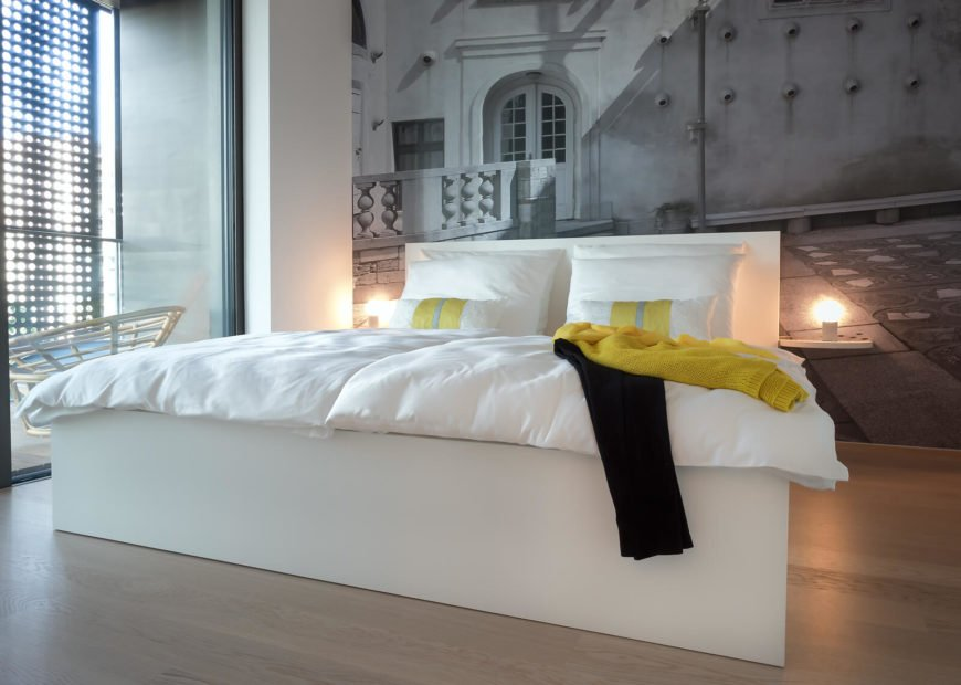 All-white frame bed stands over more natural hardwood flooring, with a massive art print photograph covering the far wall.