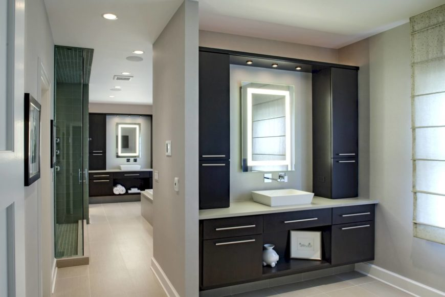 Sprawling bathroom includes two full vanities with espresso cabinetry and quarts countertops, with white porcelain vessel sinks below wall-mounted faucets. The space is another great example of the subtle deployment of embedded-lighting mirrors.