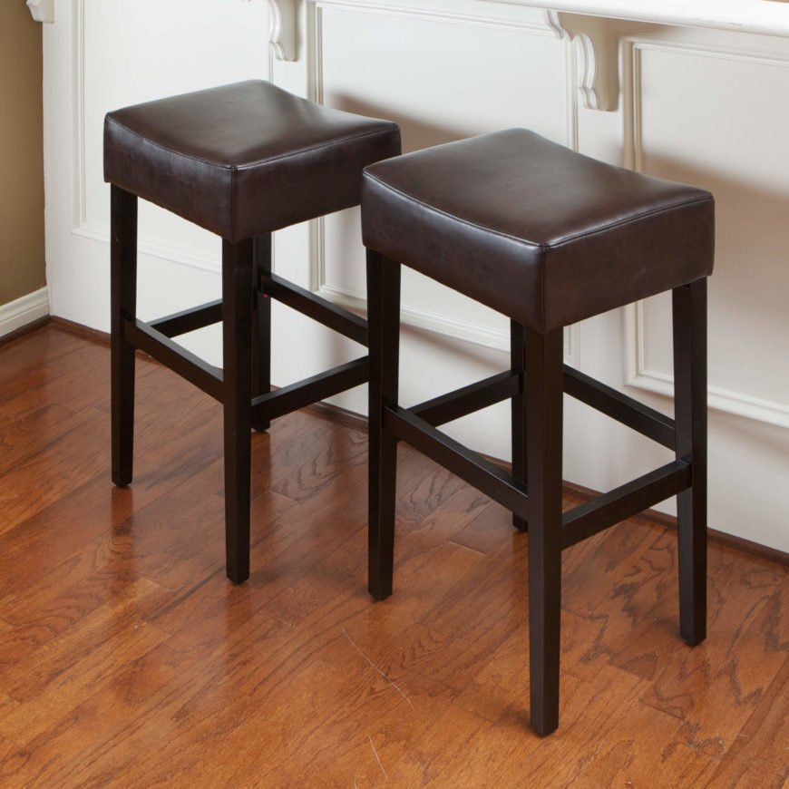 Backless leather-seat stools in the saddle-style with wooden legs.