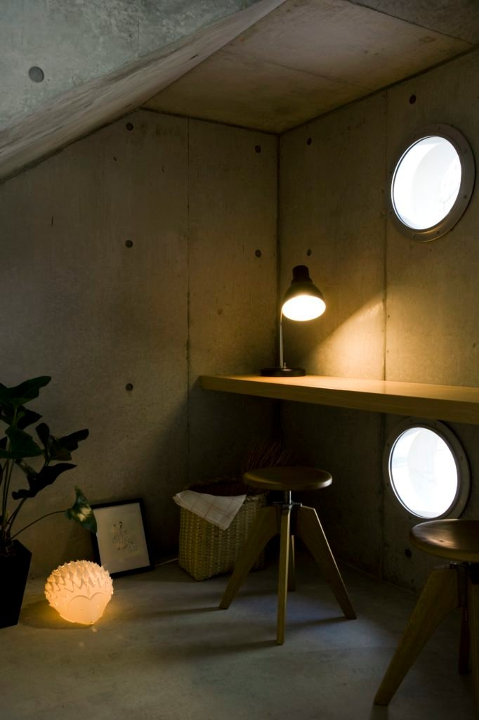 Workshop space stands just inside the vertical strip of hole windows, with more natural wood shelving built into the concrete walls, above matching stools.