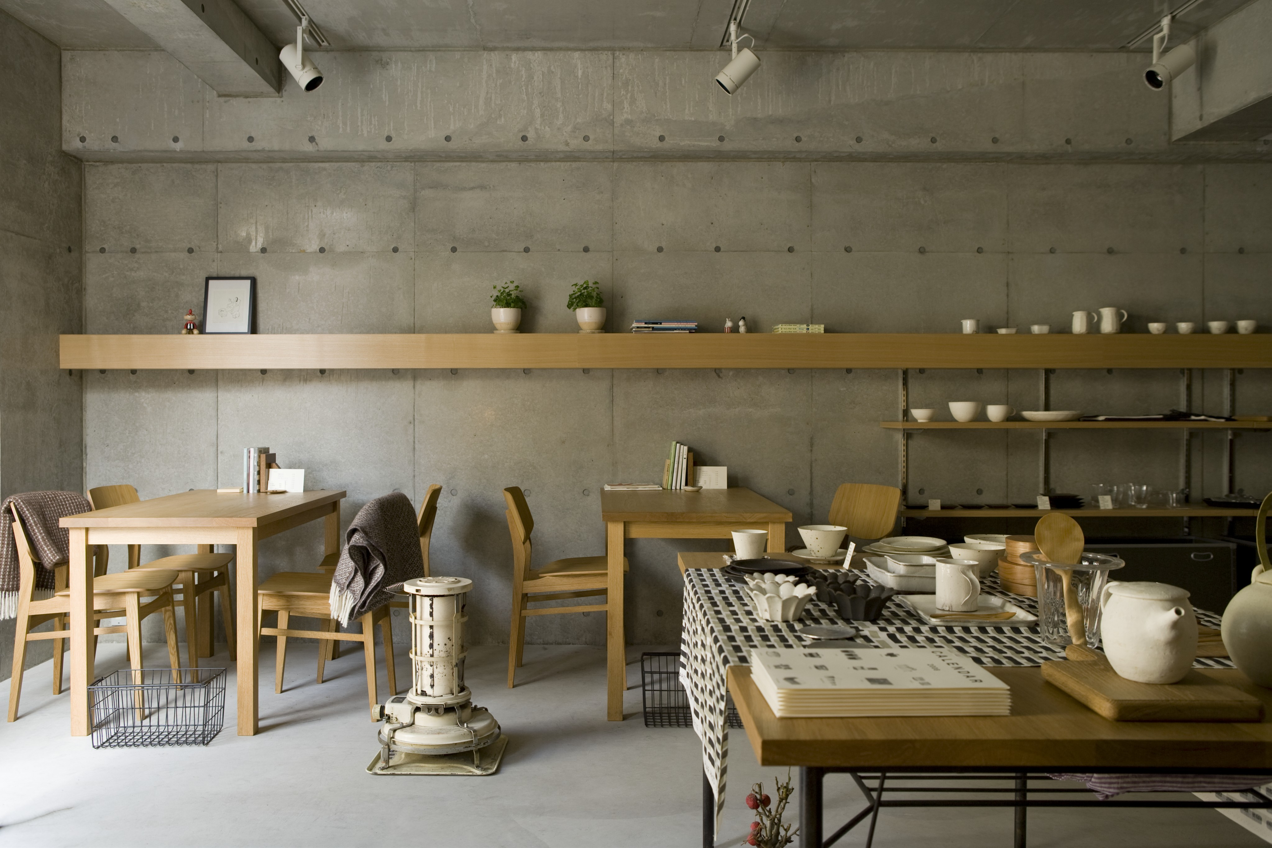 The open dining space features an array of light natural wood tables, with matching shelving running the length of the room, mounted to the concrete wall. Angled canister lights are seen above.