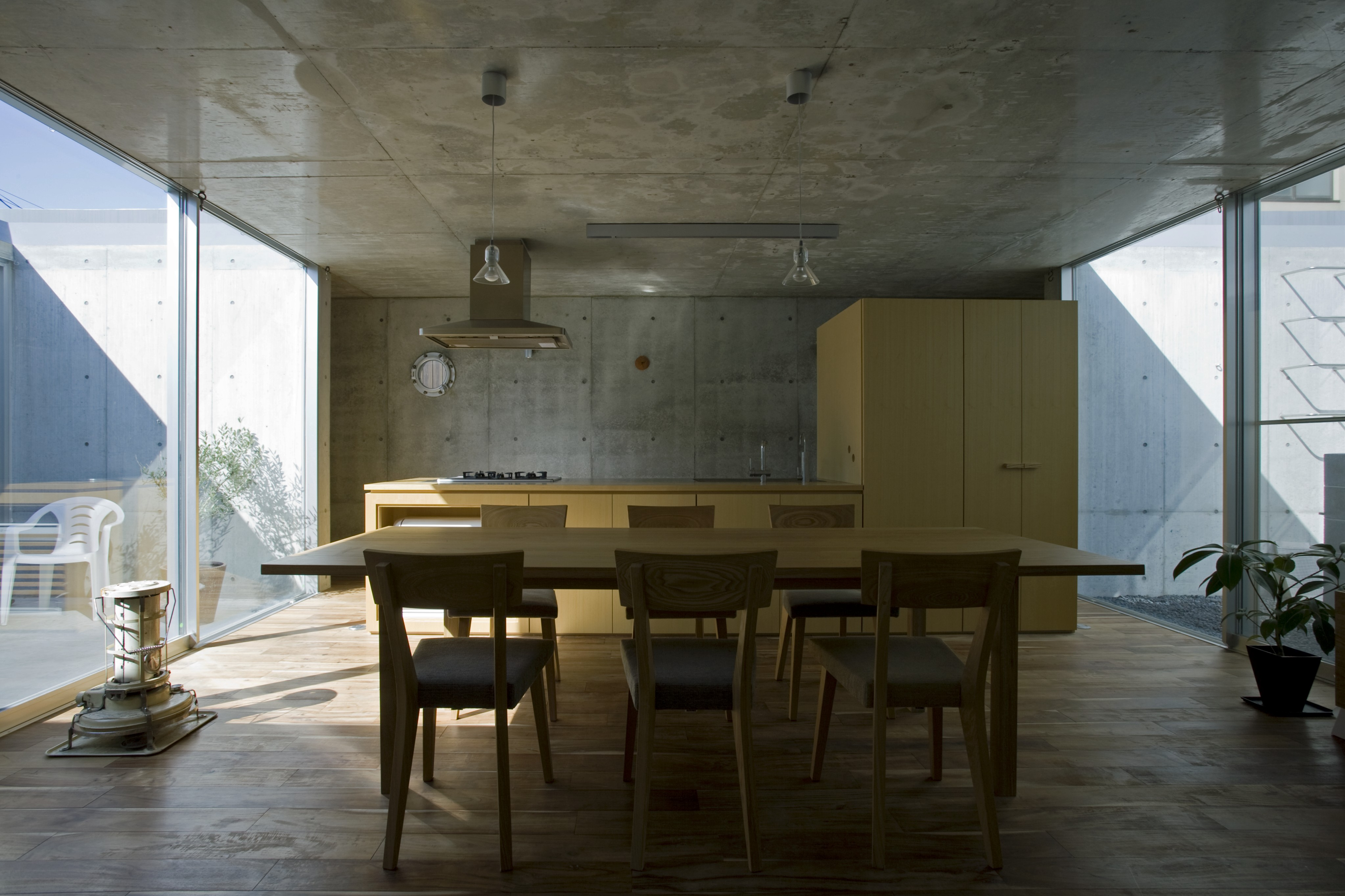 Straight on view of the kitchen and dining area. Here we see the light natural wood tones of the cabinetry and kitchen island, plus the dining set, standing out amidst the concrete grey structure.