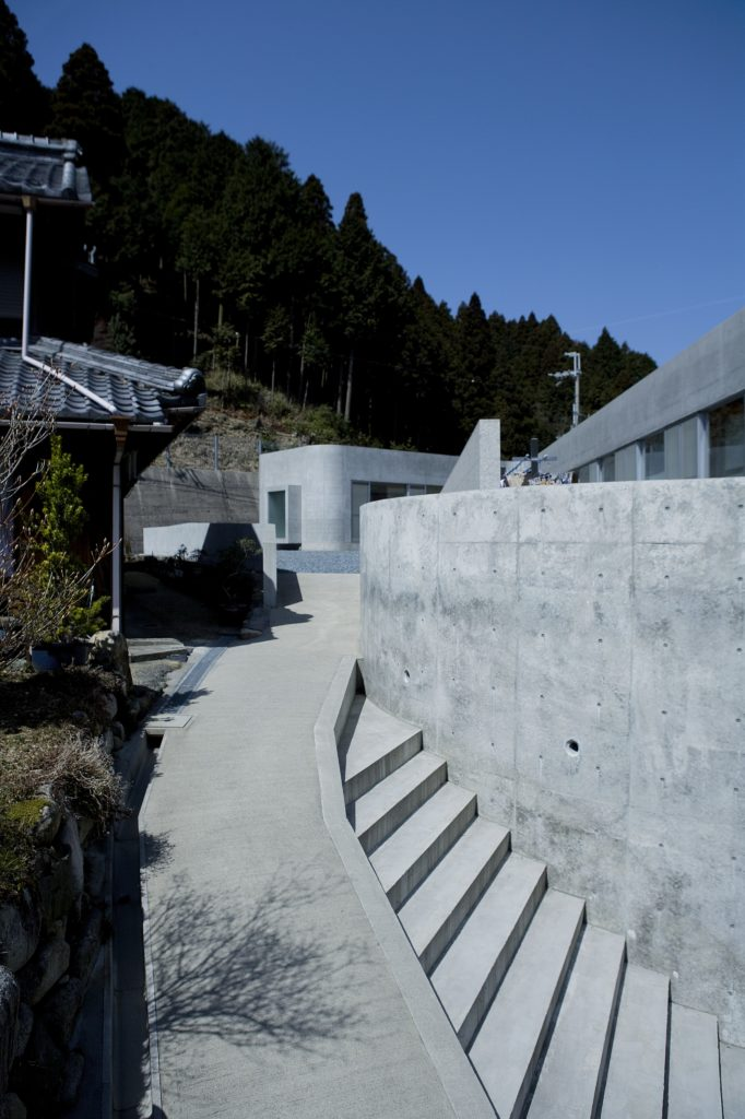 Coming up the stairway entrance from street level, we see the garden at left, with folded layers of concrete at right obscuring the home.