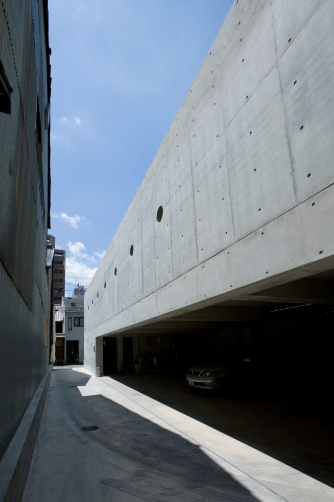 With a narrow drive running next to the home, the raised level allows for expansive, sheltered parking space beneath.