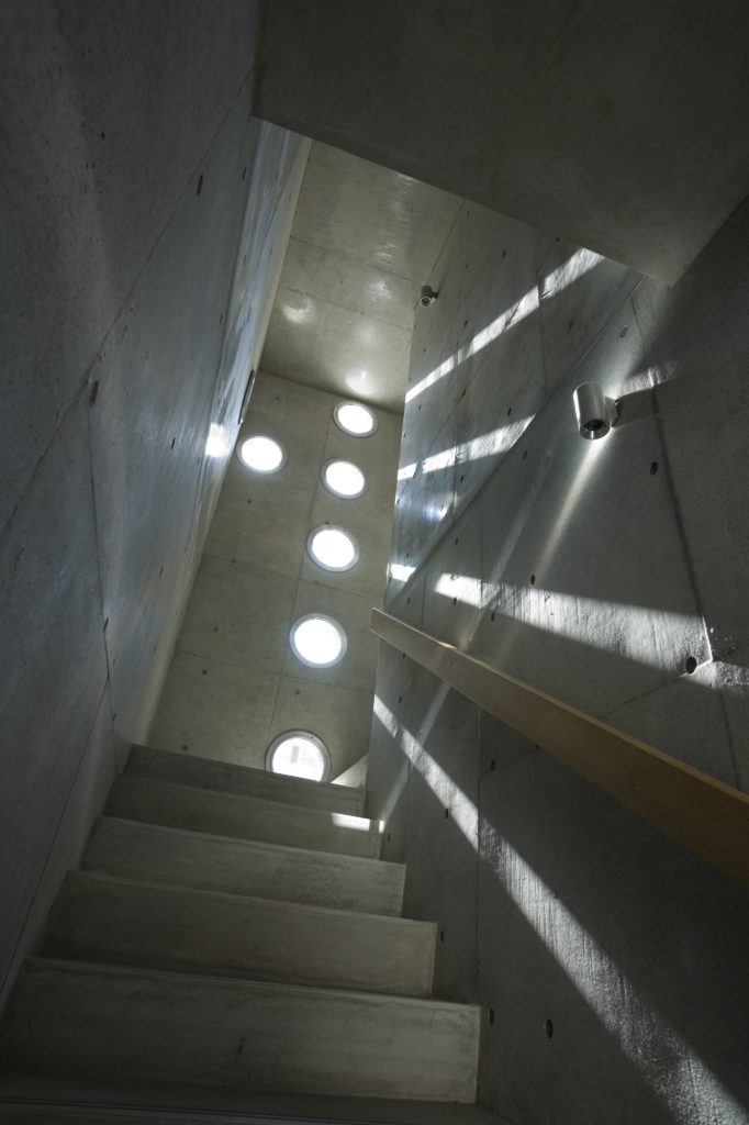 The staircase is a great example of the striking ways that the holes allow light to play in.