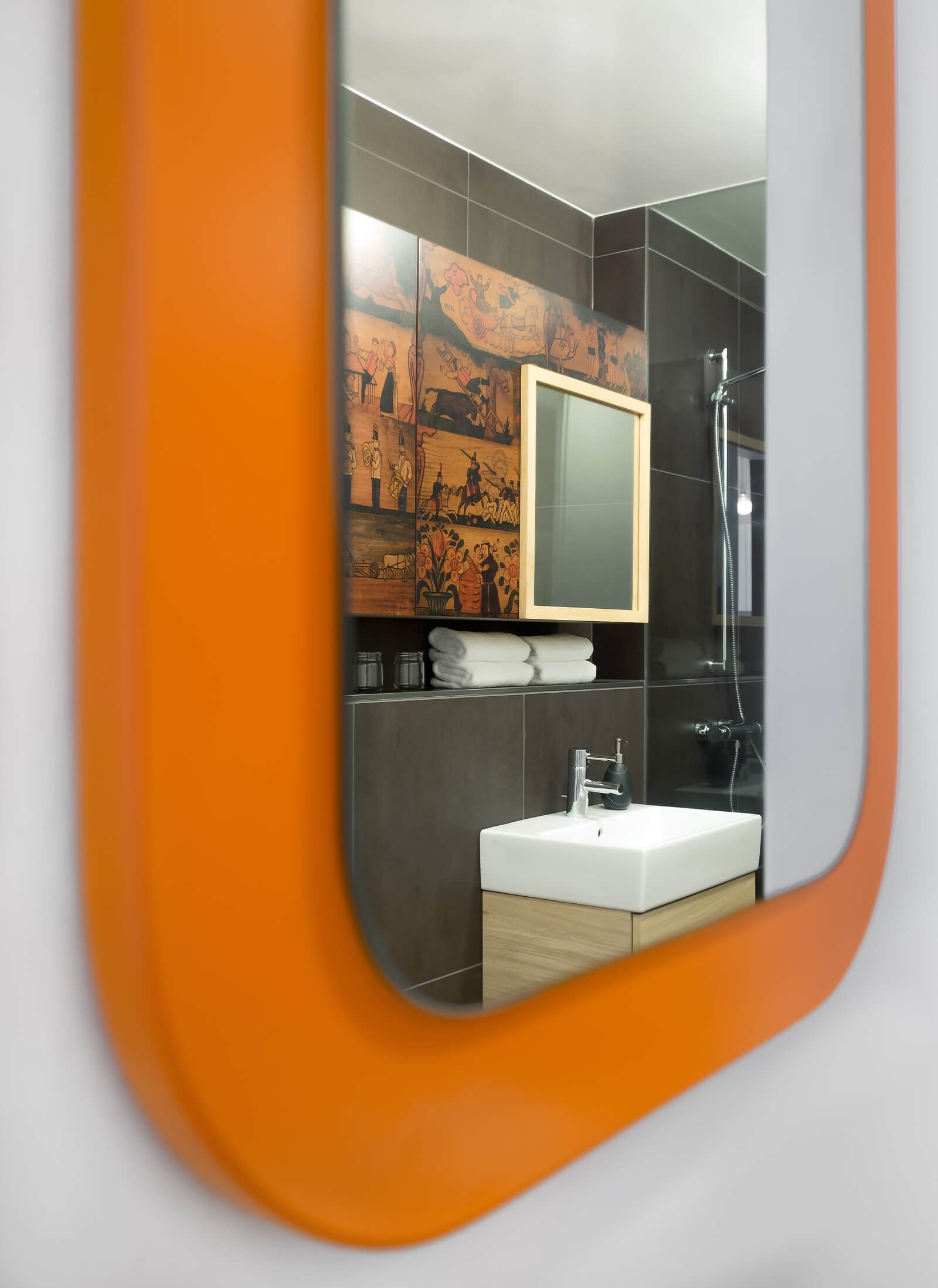Close view of the hallway mirror reveals a slice of the modern, luxurious bathroom.