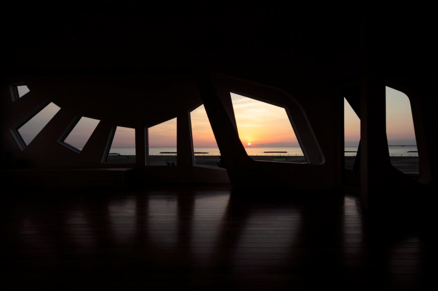 At sunrise, the room takes on a spectral quality, with cutouts framing the horizon like a series of paintings.