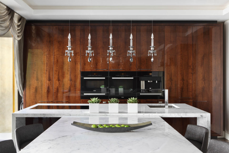Five jewel-like crystal pendant lights float above the central kitchen island, illuminating the sleek Cararra marble countertop. Appliances sit within sleek polished wood panels at rear.