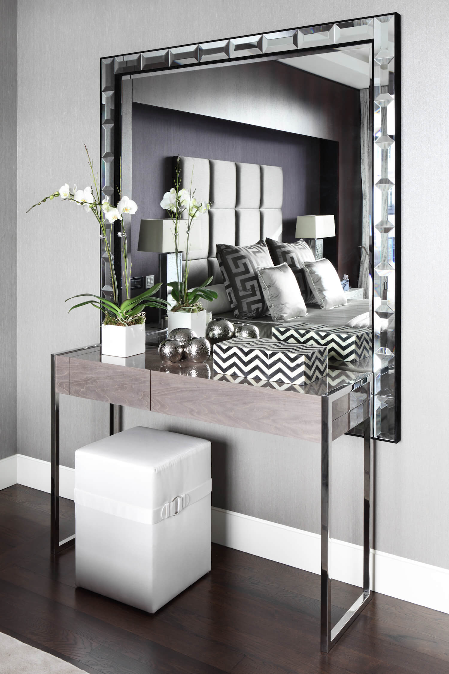 A bespoke dressing table in high gloss veneer with velvet lined storage is poised on delicate chrome legs, aiming for an air of feminine elegance.