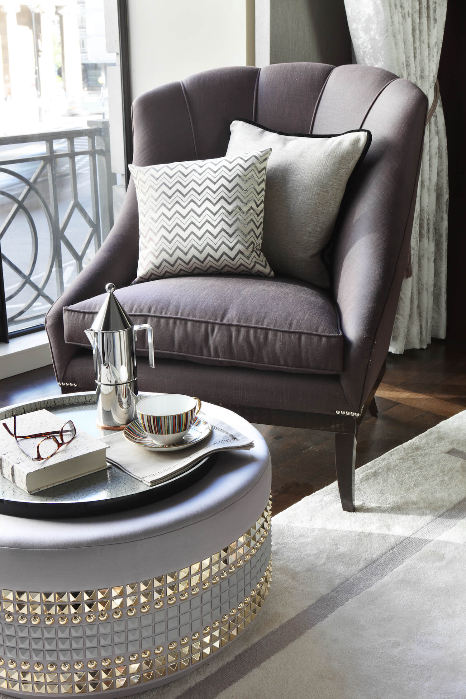 Sumptuous tonal fabrics contrast and accentuate the contemporary stud detailing on this Lee Broom footstool beside the balcony entrance.