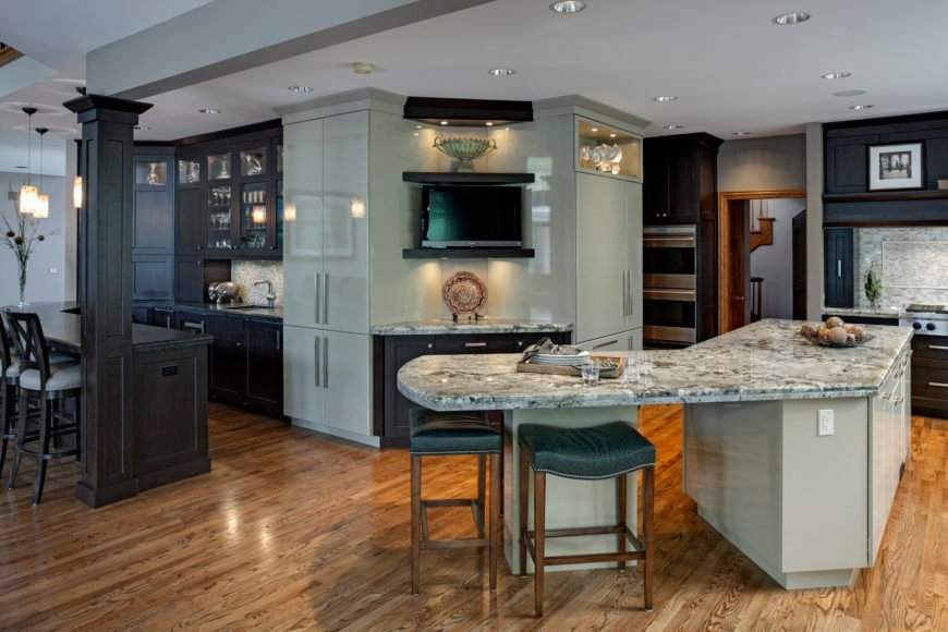 Expansive transitional kitchen features L-shaped island at right with full wraparound dining space, with high contrast cabinetry in dark wood and light grey, over natural hardwood flooring.