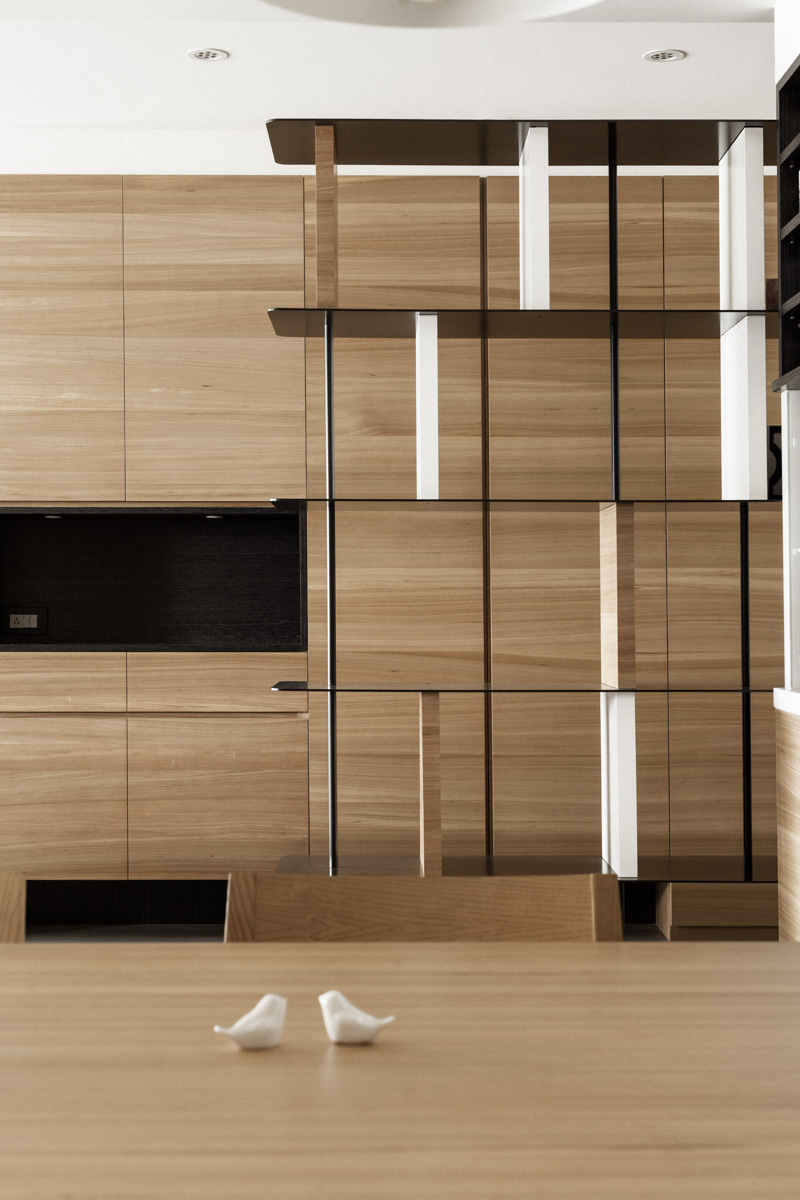 Close, zoomed view over the dining table shows how perfectly matched the natural wood is throughout the apartment.