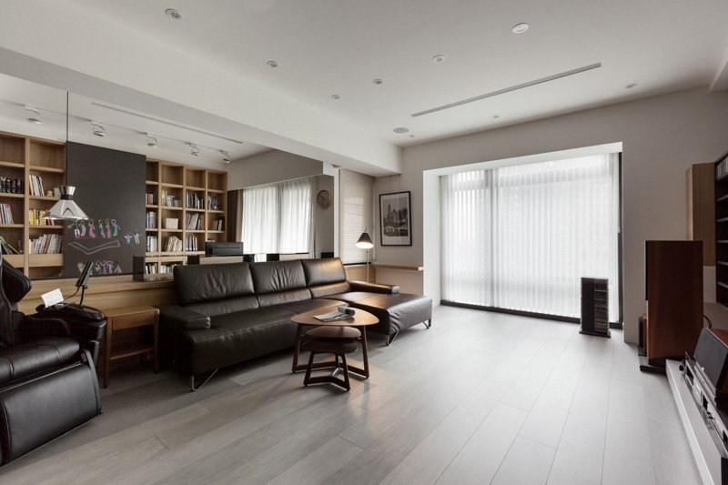 With the shades drawn, the rooms are still naturally illuminated across the expanse of light natural hardwood flooring. An array of embedded ceiling lights are scattered throughout.