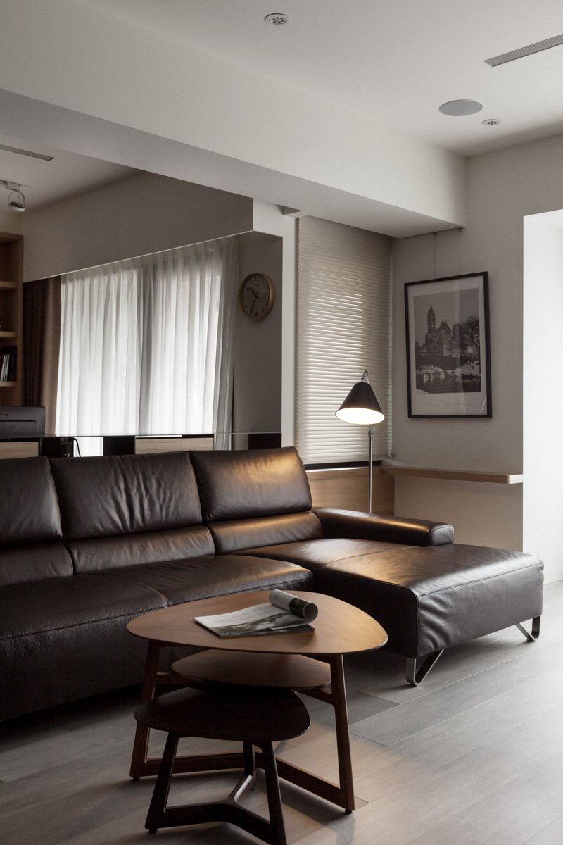 The dark mocha leather of the contemporary sectional pairs well with the lighter natural hardwood flooring and rich wood tables.