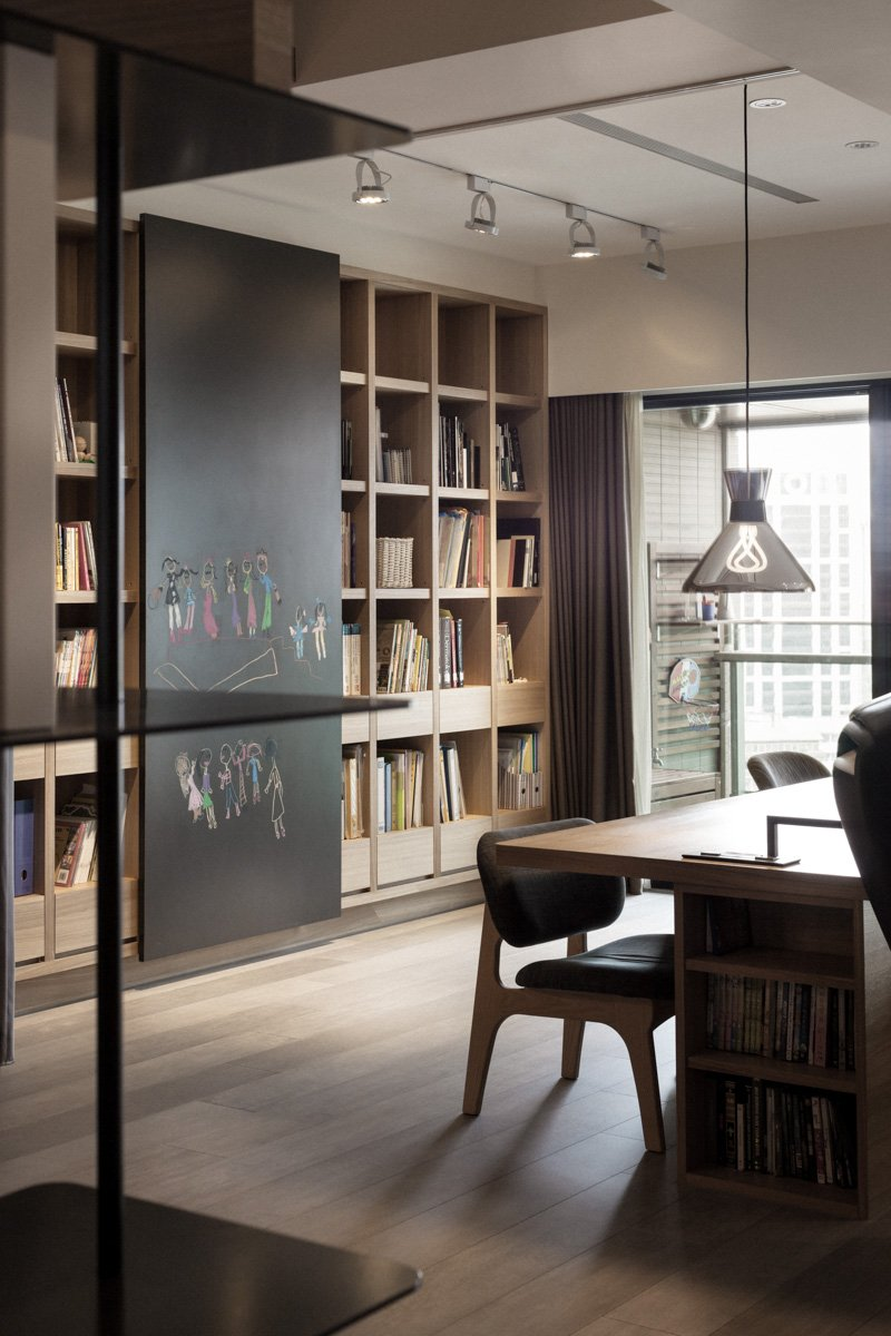 This office space is defined by the large wooden desk with built-in storage, across from wall-size natural wood shelving.