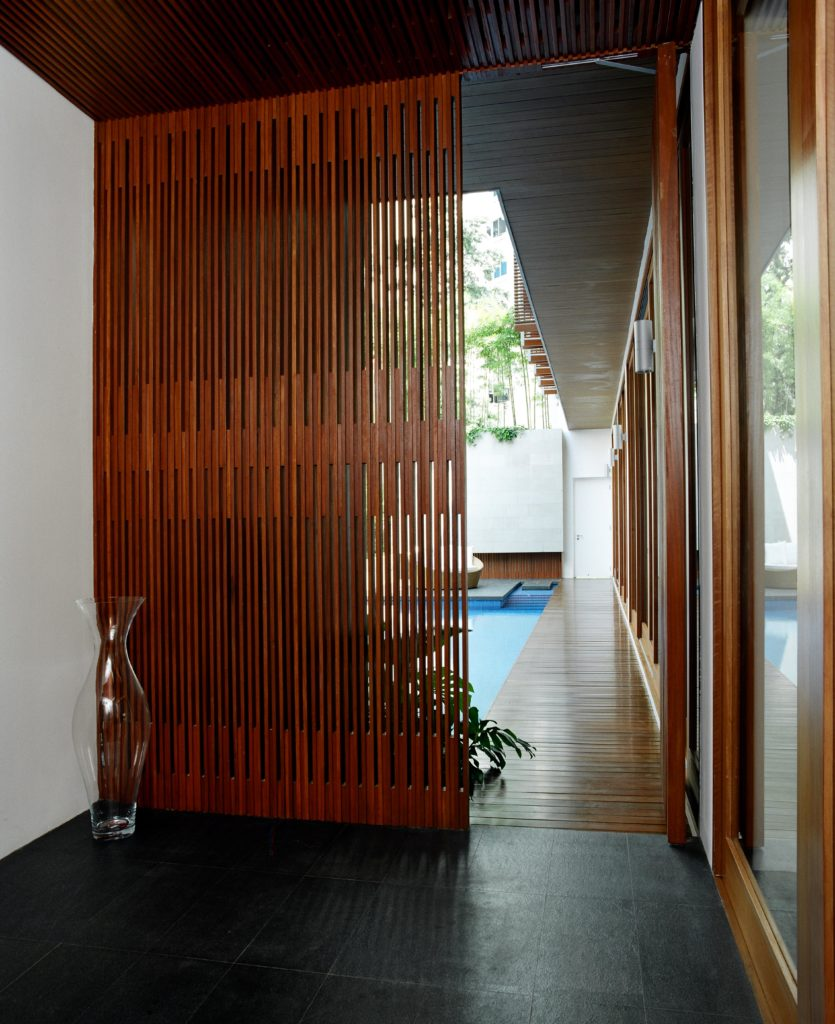 Entering the home over this black tile floor, through rich wood shades we see the inner courtyard pool area, with main living room on right behind full height glass panels.