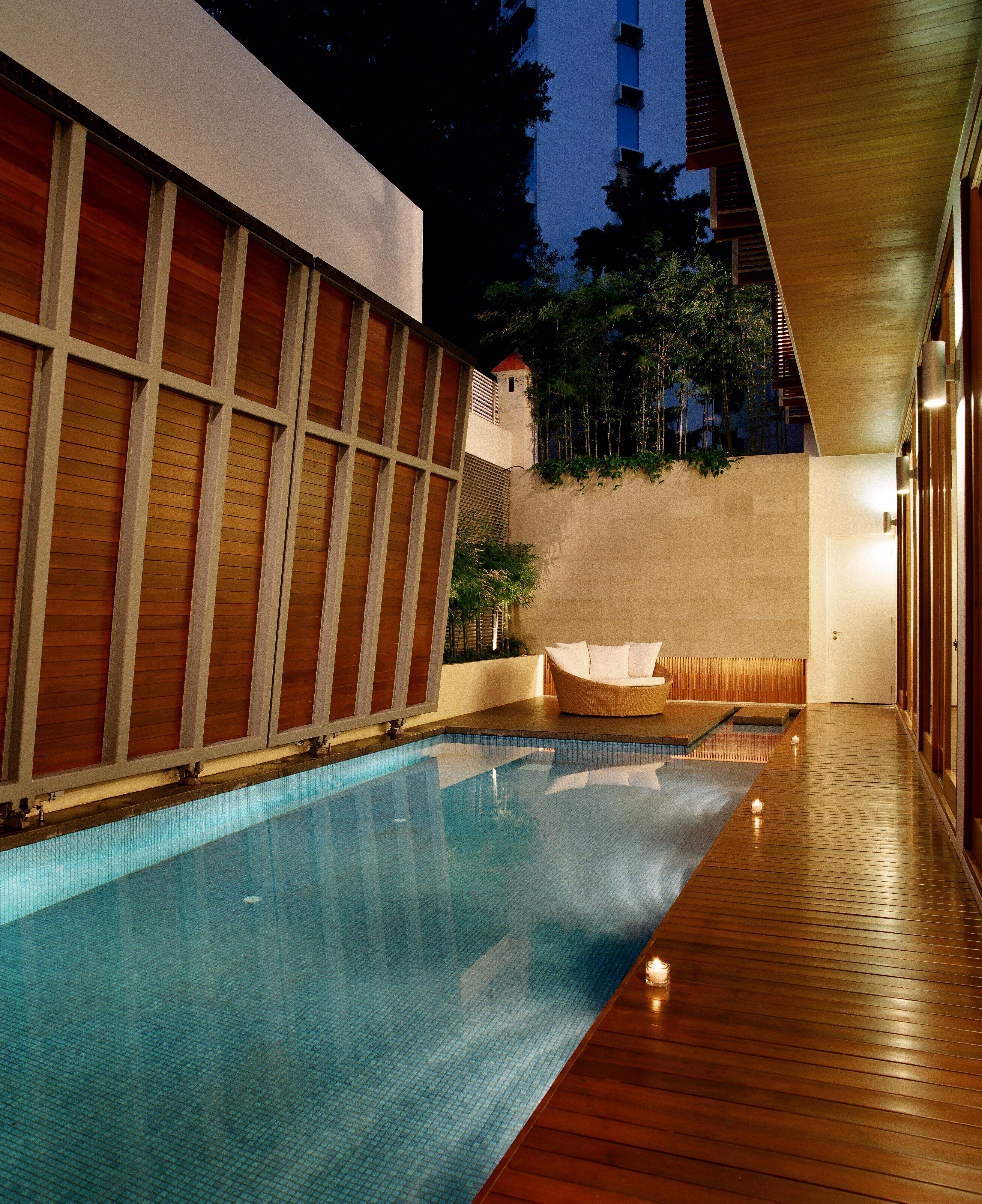 """At night, we see the inner courtyard illuminated by bi-directional sconces between the exterior glass panels, plus a row of candles placed next to the pool. The seating area at far end appears to """"float"""" upon the water."""