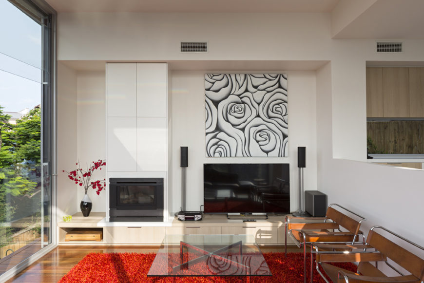 The living room holds an array of fine details: leather wrapped metal frame chairs, glass and chrome coffee table, small gas fireplace with white panel surround, and low slung natural wood media shelving across length of the space.