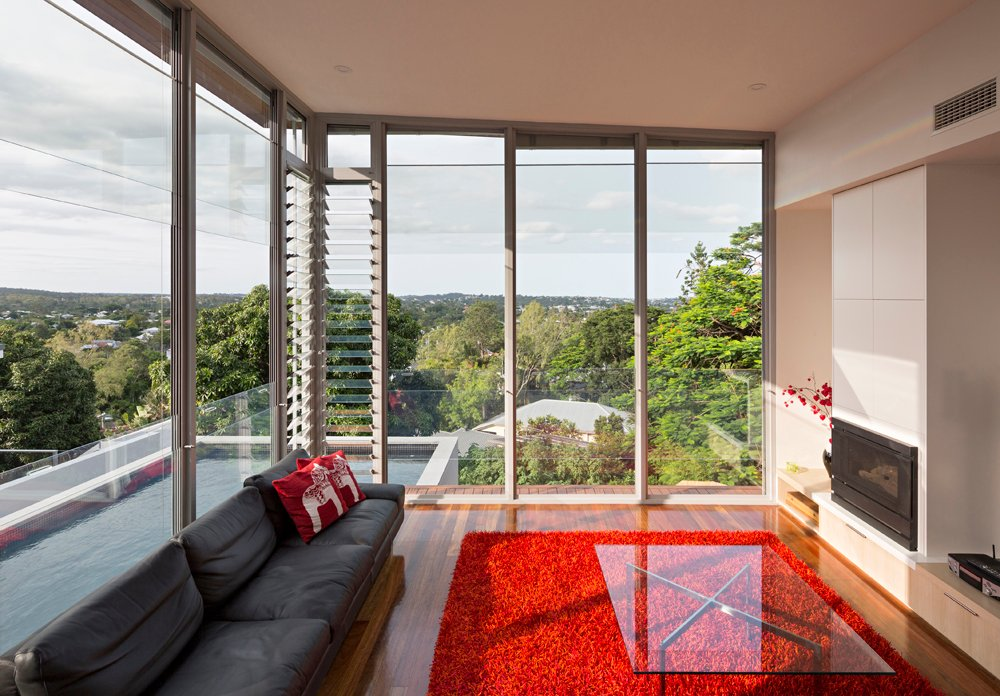 This corner room features unparalleled views of the surrounding valley and town. The rich tones stand the room apart from a mostly neutral hued home, while sliding and louvered glass windows grant the space a patio-like feel.