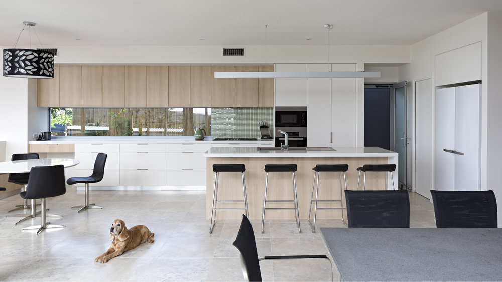 The central open kitchen and dining space contains a large dining table in grey with black and metal seating, matching the stools at the island and breakfast nook chairs. Minimalist lighting sources courtesy of leaf-print black cylindrical chandelier over nook and single 'bar' style track over island.