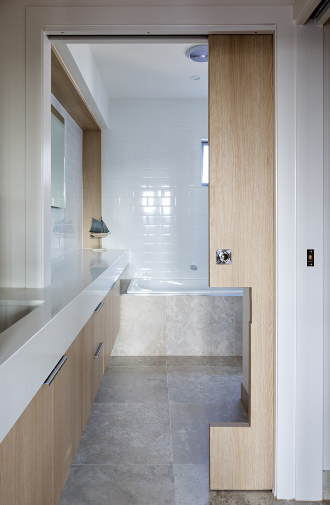 The second bathroom features this truly unique sliding wood pocket door, cut to match the contours of the countertop at left, dividing bath from vanity space.