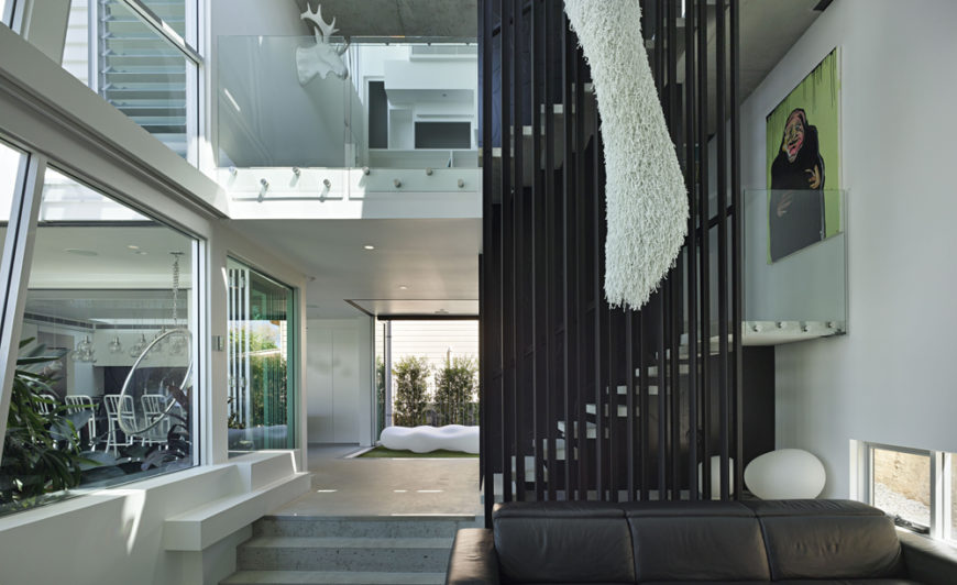 This lower landing holds a black leather sofa below the metal-wrapped staircase, with various rooms of the home seen through layers of plate glass.