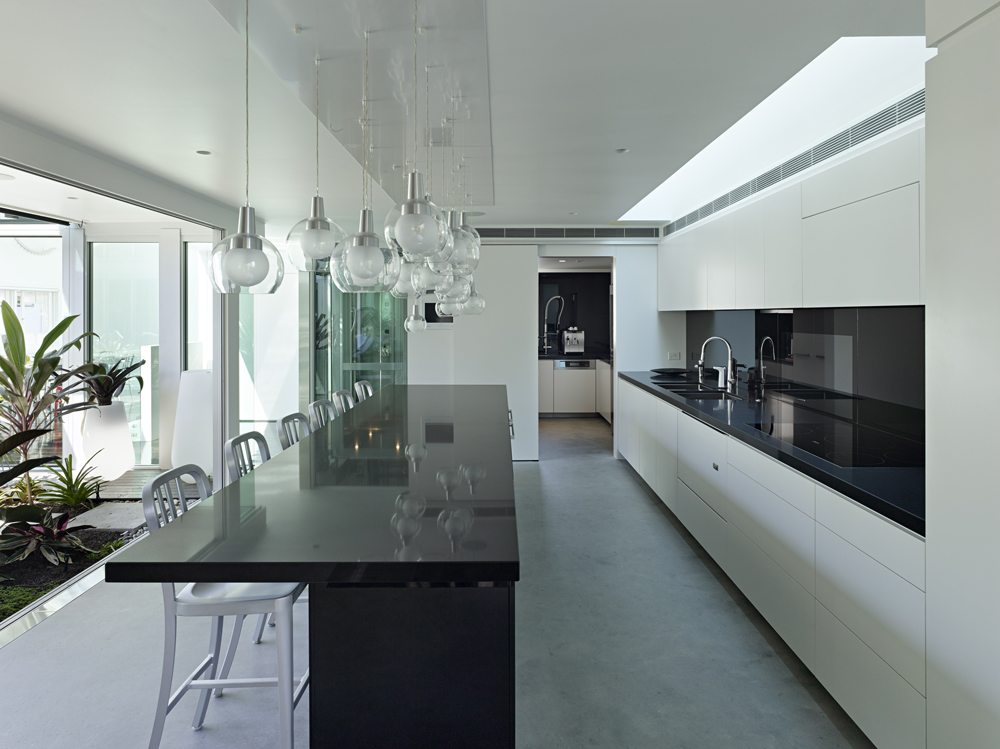 The kitchen contrasts white surroundings with jet black countertops and lengthy island, with an array of spherical glass chandeliers hanging above.