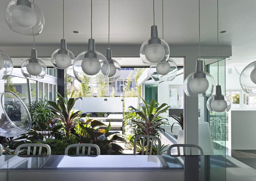 Turning back toward the rooftop garden, looking across the black island and cascading set of hung glass lamps, we see the blurred line between indoor and outdoor spaces.