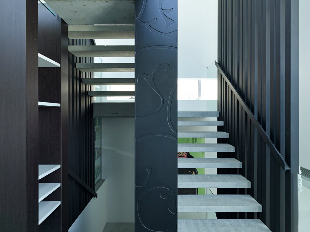 """The staircase features """"floating"""" concrete step design for maximum visibility throughout."""