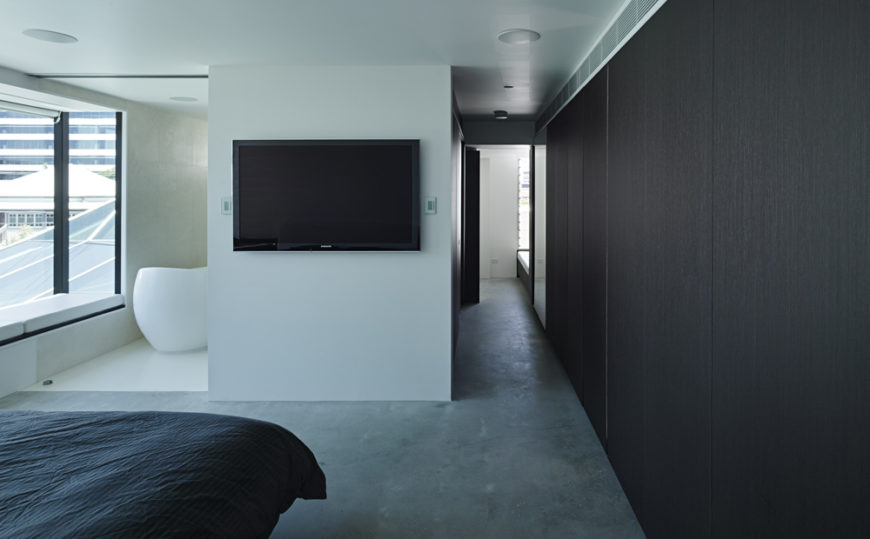 From the primary bedroom suite, we see a lengthy hallway decked in black wood at right. Single wall mounted television breaks up the white walls, with bathroom entrance at left.