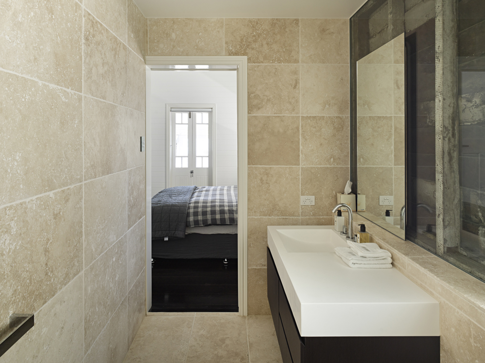 Second bathroom draped in beige tile floor to ceiling, featuring modern minimalist vanity in dark wood and white countertop, with sliding mirror at right.