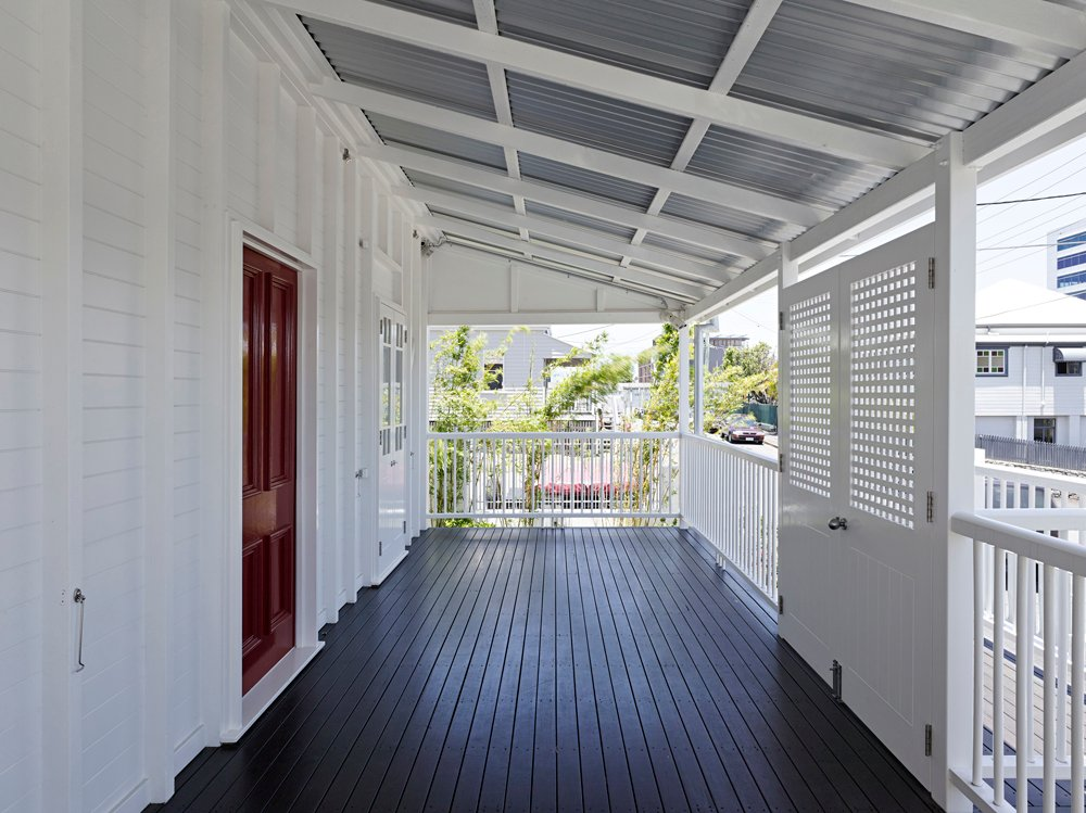 On the more traditionally fashioned street side of the home, this expansive dark wood porch is wrapped in white railings and shielded by slanted corrugated metal roof with exposed white wood beams.